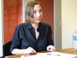 Julie Napolin in dark shirt, sitting at table