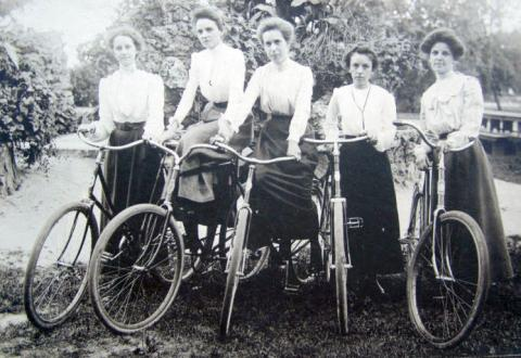 black and white photograph of five individuals in a row wearing white blouses and dark skirts holding or sitting on bicycles outdoors