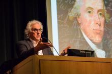 Stephen Fried lectures from a podium in from of a projection of a painting Benjamin Rush with white cursive handwriting overlaid.