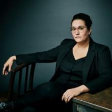 Carmen Maria Machado in black suit sitting in front of blue wall