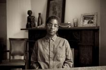 Sepia tone photography of Simone White sitting in chair with fireplace and art in background