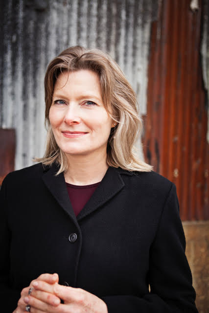 Jennifer Egan in black coat, smiling at camera