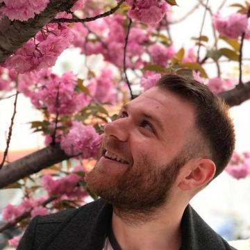 Portrait of Jacob Myers looking up at flowers in a tree