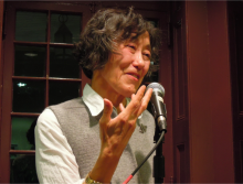 Berssenbrugge speaking into microphone at the Kelly Writers House