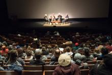 Audience looks on four speakers, seated, onstage during the No Mud, No Lotus film series