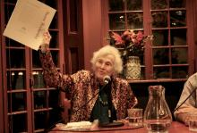 Naomi Replansky at the Kelly Writers House, speaking into microphone while holding a paper in the air for audience to see