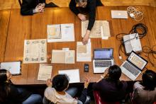 Session of Manuscript Collective session, where students and Peter Stallybrass examine documents on a wooden table in the Lea Library