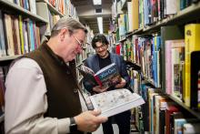 Adjunct Professor Robert Berry, left, and Assistant Professor of English Jean-Christophe Cloutier, who teach the undergraduate course Making Comics, enjoy two comics that are part of Van Pelt-Dietrich's collection, available to students, faculty, and staff.