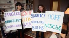From video: Emily Steiner and Aylin Malcolm in academic office in front of bookcases hold up four white posters with 11 hand-lettered words written in  bright-colored marker