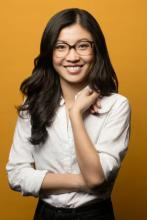 Weike Wang in white shirt, smiling at camera, in front of a yellow wall