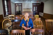 Deb Burnham, smiling, sits in row of chairs in Kelly Writers House