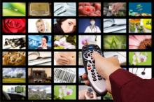 hand holding remote in front of a screen subdivided into a 6x6 grid of varied, colorful images (such as a close-up of a rose, a woman speaking on a headset, and a fireplace) separated by black borders