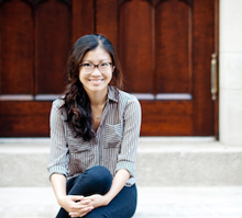 Weike Wang sitting on stairs, legs crossed, smiling, in front of wooden doors