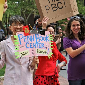 Chi-ming Yang and other marchers hold signs in support of Penn Book Center at rally on Locust Walk