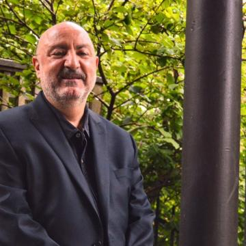 Anthony DeCurtis in black suit and shirt smiling at camera outside of building