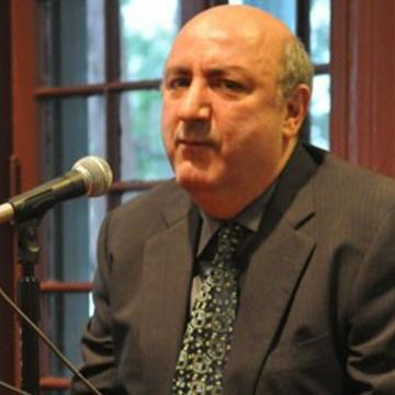 Professor Anthony DeCurtis, sitting, speaks into microphone in Kelly Writers House