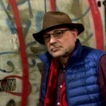 Charles Bernstein, wearing a red shirt, blue vest, and brown hat, stands in front of colorful art