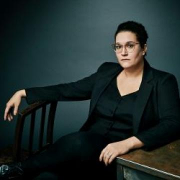 Carmen Maria Machado in black suit sitting in front of blue wall