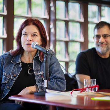 Rosanne Cash speaks into microphone while sitting at a table at the Kelly Writers House next to Al Filreis