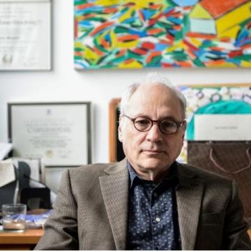 Charles Bernstein at his desk with a colorful painting by his wife hanging on wall behind him