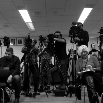 Journalists sitting on chairs on their phones in front while others man tripod-supported video cameras, in black & white